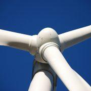 white wind turbine coating on a windmill against blue sky