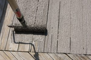 wood coatings being applied with a roller to a wooden decking