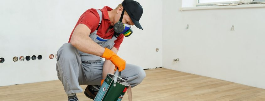 man with safety gear applying wood coatings to a floor